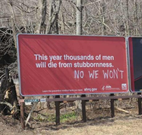 """Sign: """"This year thousands of men will die from stubbornness."""" Grafitti: """"NO WE WON'T"""""""